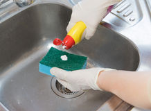 Homework. Cleaning of the kitchen sink. Cleaning of the kitchen sink Woman is applying a cleaner to a sponge royalty free stock photo
