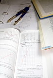 Homework college. Written homework for a technical college with circle is held on on a block. Surrounded by some school books for mathematics, physics and stock images