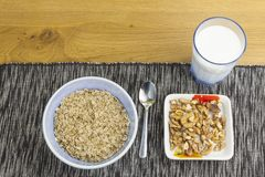 Homework diet breakfast, oatmeal with nuts and milk Royalty Free Stock Photos