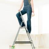 Homework DIY fun. Legs of woman climbing stepladder holding paint roller Royalty Free Stock Photo
