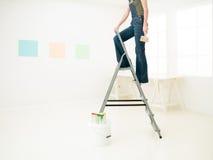 Homework DIY fun. Legs of woman on stepladder painting Stock Image