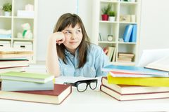 Homework doer. Cute girl being tired of doing homework Royalty Free Stock Photos