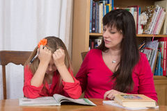 Homework Frustration. A mother consoles her young daughter when she gets discouraged trying to do her homework Royalty Free Stock Photo