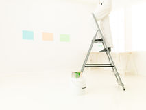 Homework fun indoor. Legs of man on stepladder painting, bright white  home. repair, building, renovation and people concept Royalty Free Stock Photo