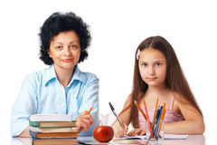 Homework With Granny. Granddaughter with her grandmother sitting under the table with books looking at you Royalty Free Stock Images