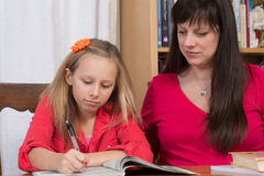 Homework Help. A young girl does her homework as her mother looks on Royalty Free Stock Photos