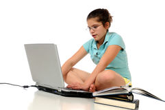 Homework on the Laptop. A preteen girl sitting on the floor doing homework on her laptop.  Isolatedon white Royalty Free Stock Photos