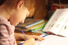 Homework preparation. Young girl doing her homework Royalty Free Stock Photos