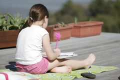 Homework Sunshine. A young girl does her homework in the sunshine Stock Photos