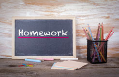 Homework text on a blackboard. Old wooden table with texture Stock Photography
