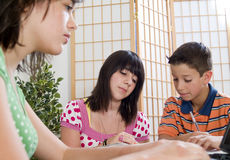 Homework Time. Three kids studying together with focus on girl in foreground stock image