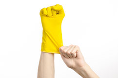Homework, washing and cleaning of the theme: man's hand holding a yellow and wears rubber gloves for cleaning isolated on white ba. Ckground Royalty Free Stock Image