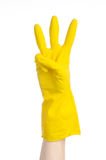 Homework, washing and cleaning of the theme: man's hand holding a yellow and wears rubber gloves for cleaning isolated on white ba. Ckground Royalty Free Stock Photo