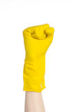 Homework, washing and cleaning of the theme: man's hand holding a yellow and wears rubber gloves for cleaning isolated on white ba Stock Image