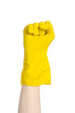 Homework, washing and cleaning of the theme: man's hand holding a yellow and wears rubber gloves for cleaning isolated on white ba. Ckground Stock Images