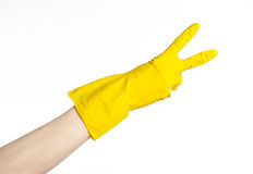 Homework, washing and cleaning of the theme: man's hand holding a yellow and wears rubber gloves for cleaning isolated on white ba Royalty Free Stock Image