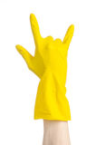 Homework, washing and cleaning of the theme: man's hand holding a yellow and wears rubber gloves for cleaning isolated on white ba. Ckground Royalty Free Stock Images