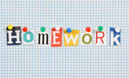 Homework. The word Homework in cut out magazine letters pinned to a background of blue graph paper Royalty Free Stock Photography
