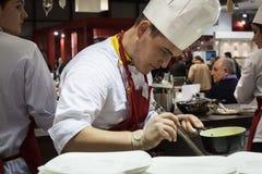 年轻人烹调在他的食谱在HOMI,家国际展示的工作在米兰,意大利 免版税库存图片