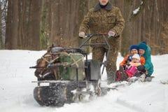 HOMIEL', BIELORUSSIA - 15 GENNAIO 2017: Divertimento di inverno Gatto delle nevi sledging di caccia della famiglia Fotografie Stock