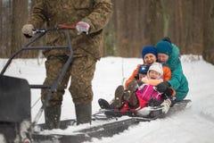 HOMIEL', BIELORUSSIA - 15 GENNAIO 2017: Divertimento di inverno Gatto delle nevi sledging di caccia della famiglia Immagini Stock
