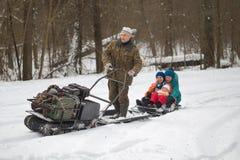 HOMIEL', BIELORUSSIA - 15 GENNAIO 2017: Divertimento di inverno Gatto delle nevi sledging di caccia della famiglia Fotografia Stock