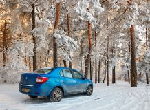 Homiel', Bielorussia - 24 gennaio 2018: un'automobile blu RENAULT LOGAN ha parcheggiato nella foresta dell'inverno Fotografie Stock