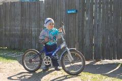 Homiel', Bielorussia - 4 maggio 2015: i bambini del villaggio guidano le bici e la riparazione loro immagini stock
