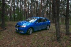 HOMIEL', BIELORUSSIA - 24 MAGGIO 2017: L'automobile blu di RENO LOGAN ha parcheggiato in un'abetaia scura Immagini Stock Libere da Diritti