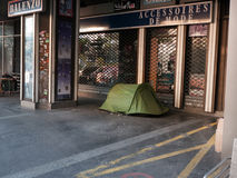 Homeless people camping in Paris. Homeless people find shelter in a tent they pitched on the sidewalk in one of the busy commercial areas in Paris Stock Image