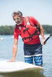 Homme à côté de panneau de palette comique sur le lac Photos stock