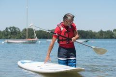 Homme à côté de panneau de palette comique sur le lac Image stock