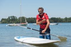 Homme à côté de panneau de palette comique sur le lac Photo stock