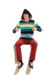 Homme à capuchon s'asseyant sur une bannière avec des pouces  Images stock