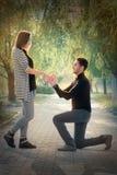 Homme à genoux proposant avec une bague de fiançailles Image libre de droits