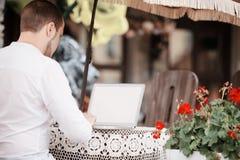 Homme à l'aide d'un ordinateur portable moderne sur une table extérieure Photos stock