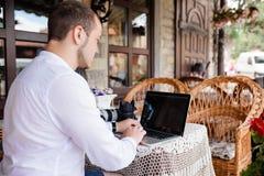 Homme à l'aide d'un ordinateur portable moderne sur une table extérieure photographie stock