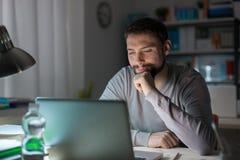 Homme à l'aide d'un ordinateur portable tard la nuit photographie stock