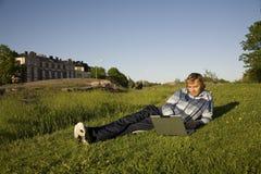 Homme à l'aide d'un ordinateur portatif à l'extérieur Photo stock
