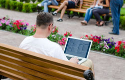 Homme à l'aide d'un ordinateur portatif dans un stationnement public images libres de droits