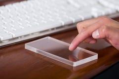Homme à l'aide d'un téléphone intelligent transparent futuriste sur une table en bois Images stock
