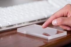 Homme à l'aide d'un téléphone intelligent transparent futuriste sur une table en bois Photo stock