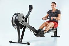 Homme à l'aide d'une machine de presse dans un centre de fitness photographie stock libre de droits