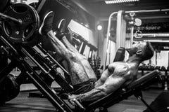 Homme à l'aide d'une machine de presse dans un centre de fitness Homme fort faisant un exercice sur ses pieds dans le simulateur images libres de droits
