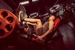 Homme à l'aide d'une machine de presse dans un centre de fitness Image modifiée la tonalité images libres de droits