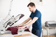 Homme à l'aide d'une presse de serigraph photos libres de droits