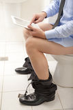Homme à l'aide d'une tablette tout en se reposant sur la toilette. Images libres de droits