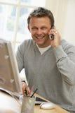 Homme à l'aide de l'ordinateur et parlant au téléphone Images stock