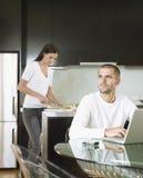 Homme à l'aide de l'ordinateur portable avec la femme préparant la nourriture Photos libres de droits