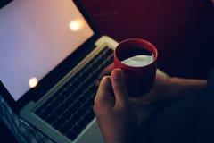 Homme à l'aide de l'ordinateur portable dans la maison avec la tasse de café Images stock